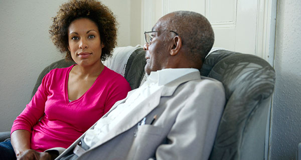 Adult daughter sitting with older father