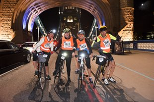 4 cyclists on a bridge at night