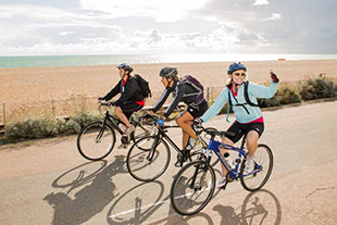 3 cyclists riding near sea