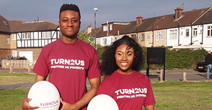 two young people in field wearing turn2us t-shirts holding balls