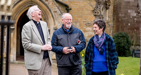 Three Anglican priests laughing together