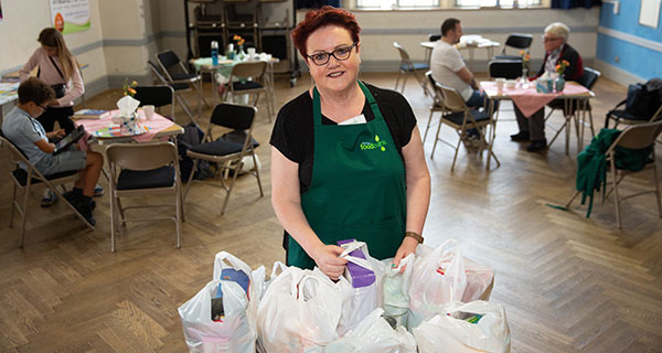 Trussell Trust volunteer with food bank bags