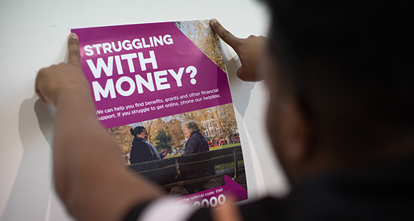 Man putting up struggling with money poster