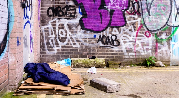 A sleeping bag and cardboard boxes on the ground in an alleyway behind an office block