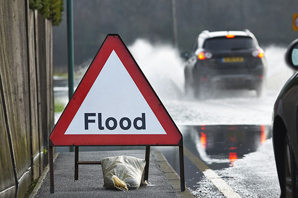 "A road sign saying ""Flood"""