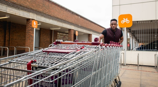 man pushing supermarket trollies