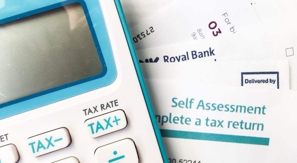 Photo of a calculator and a self assessment tax form