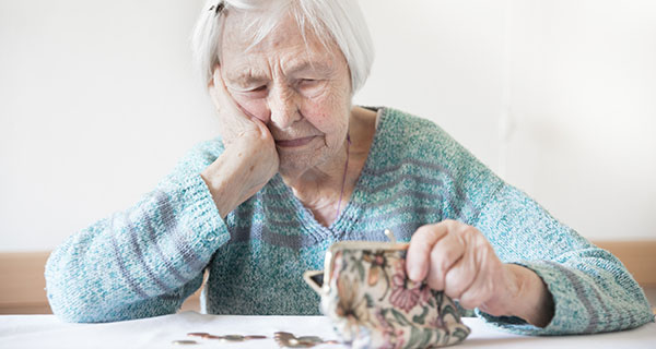 Older lady looking at coins and holding her purse