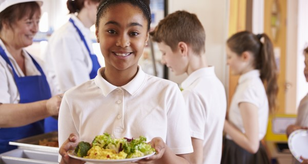 A schoolgirl with a school meal