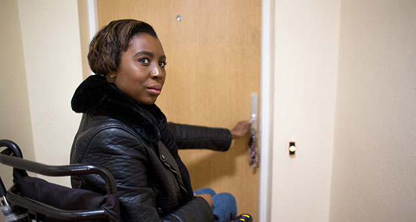 Young woman sitting in a wheelchair opening the door to her flat