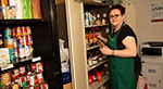 Food bank worker with food cupboards