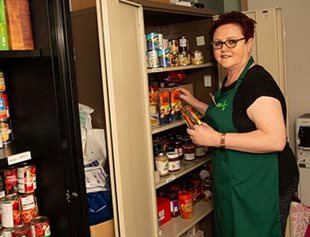 Foodbank worker with food cupboard