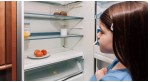 Young girl looking into an empty fridge