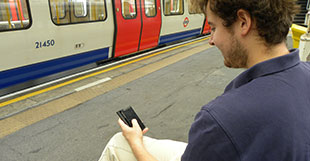 Man looking at his phone on a London Underground station