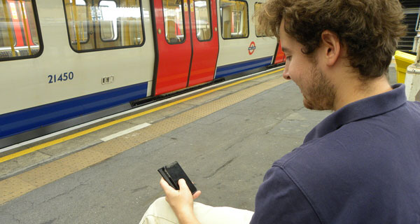 Young man with a mobile phone on a London tube station