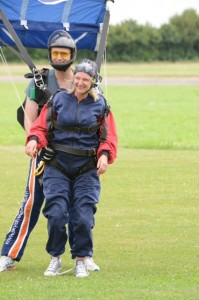 Fund raiser in parachuting clothing landing in a field